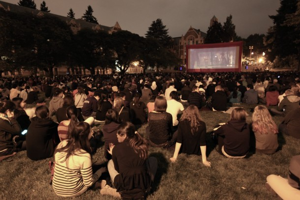 Students sitting on lawn watching a movie