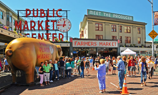 Pike place market with sign and people walking around